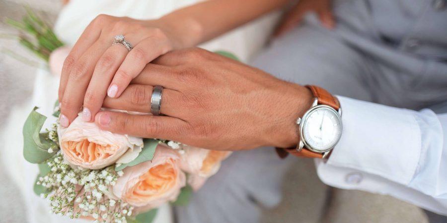 左手の薬指に指輪をはめた男性と女性が手を握っている
